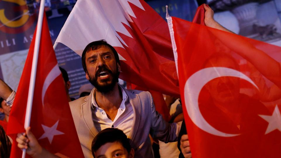 People shout slogans as they hold Turkish and Qatari flags during a demonstration in favour of Qatar in central Istanbul. Qatar has also been asked to reduce trade ties with Iran in line with the current US sanctions on the country which may prove difficult owing to the Qatar-Iran shared offshore natural gas field that supplied the former nation. (Murad Sezer / Reuters)