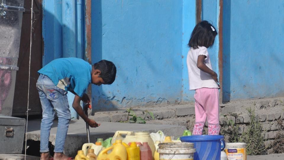 Children collect water from a public tap in Dehradun.