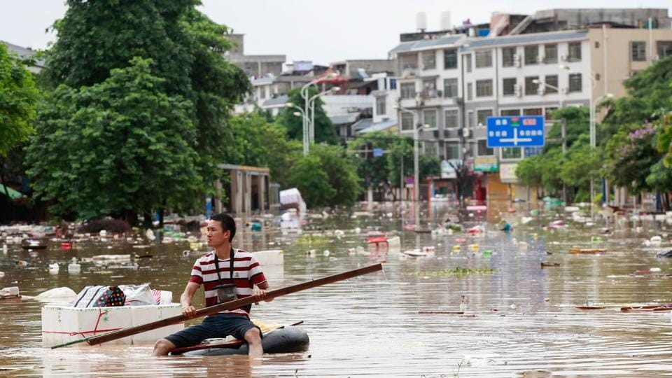 A man uses an improvised flotation device to move through floodwaters on a flooded street in Guangxi province. Rainstorms have triggered floods across central and southern China, forcing hundreds of thousands of people from their homes and leaving more than two dozen dead or missing.  (AFP)