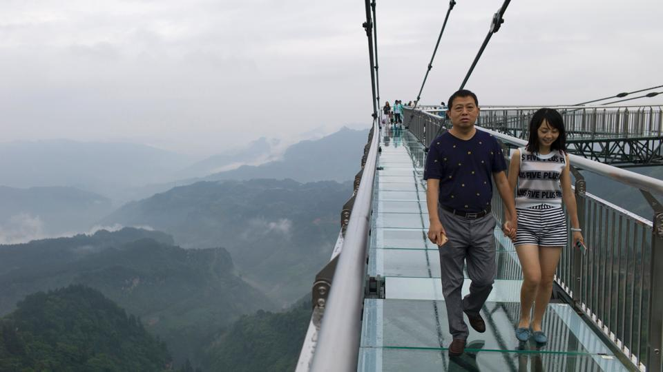 A couple walks on a glass-bottomed skywalk, certified as the world's longest, at the Ordovician park in Wansheng, China.