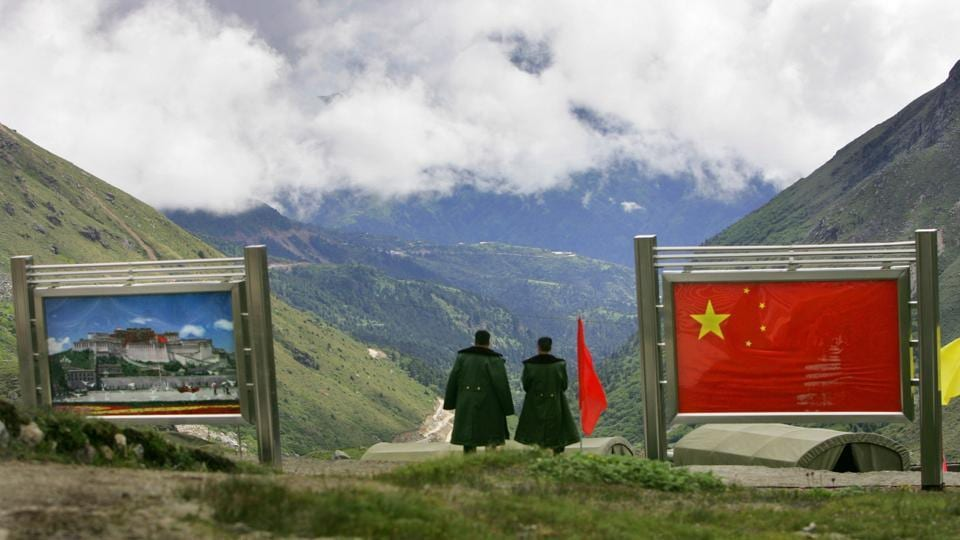 Nathu La - Indo-China Border - Chinese army officers oversee preparations as they stand between pictures of the Patola Palace, left, and the Chinese flag, on the Chinese side of the international border at Nathula Pass, in Sikkim.