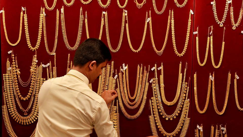A salesman arranges gold ornaments, on a display board, inside a jewellery showroom in Kochi.