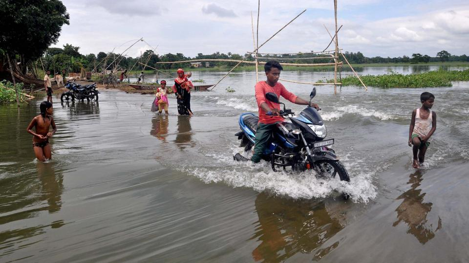 Man rides bike through water looged road in the flood affected Morigaon district of Assam.  (PTI)