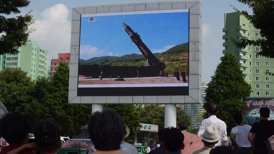 Pyongyang residents watch the news on the successful launch of the intercontinental ballistic missile on a big screen near the Pyongyang Railway Station in Pyongyang.  (AFP)