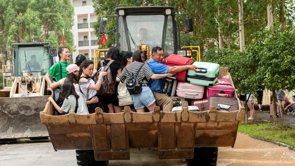 Students are transferred by a bulldozer through a flooded area in  China.  (REUTERS)