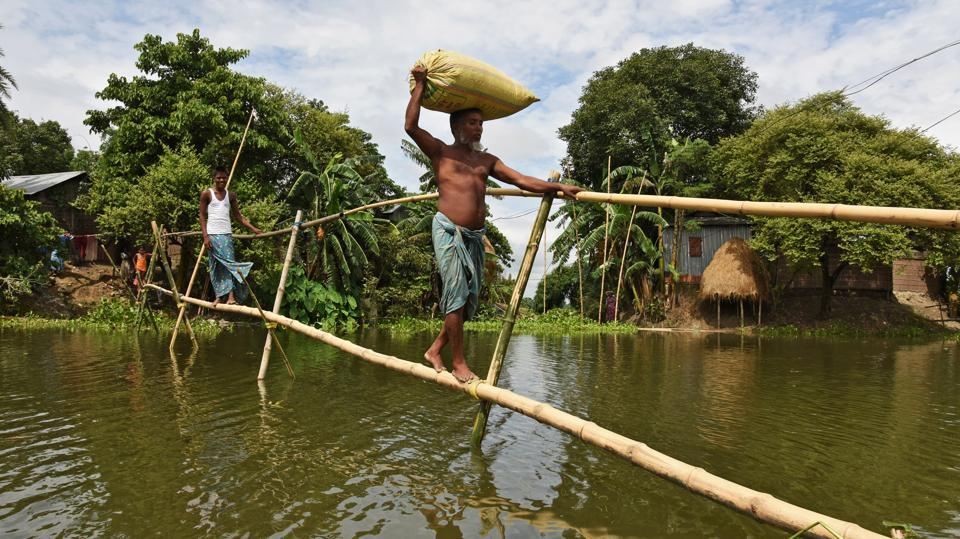 Villagers use a makeshift bamboo bridge to move across flooded areas of Morigaon district in the northeastern state of Assam. Over three lakh people are affected by the impact of  floods in eight districts. According to a report by Assam State Disaster Management Authority (ASDMA), 453 villages are currently under water with more than 15,000 people living in 66 relief camps. (Anuwar Hazarika / Reuters)
