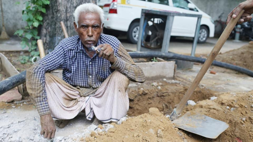 Meer Chand is a daily wager, we meet him while he is digging the pavement for underground cables to be installed.