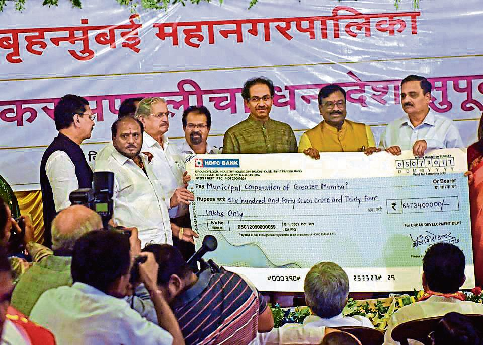 State finance minister Sudhir Mungantiwar (in yellow) handed over a Rs647.34-crore cheque — the first of many payments compensating the civic body for its post-GST octroi loss — at BMC headquarters on Wednesday.