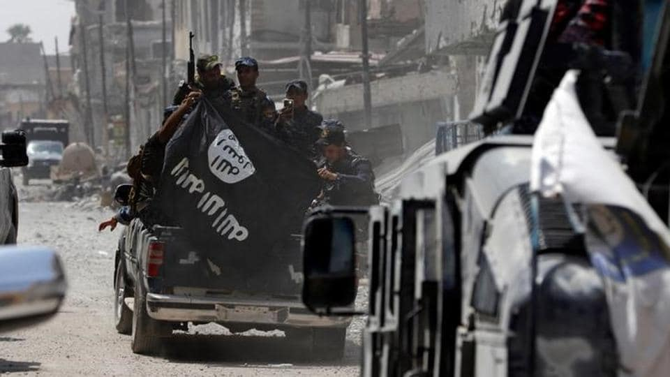 Iraqi Federal Police members hold an Islamic State flag which they pulled down during fighting between Iraqi forces and Islamic State militants in the Old City of Mosul. (Ahmed Saad / Reuters)