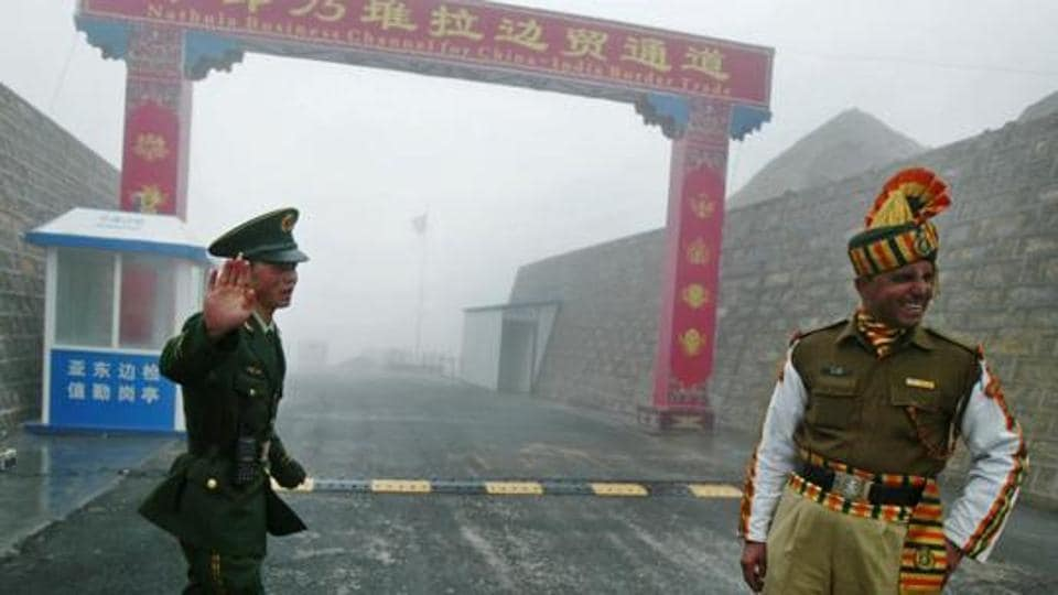 In this photograph taken on July 10, 2008, a Chinese soldier (L) and an Indian soldier stand guard at the Chinese side of the Nathu La border crossing between India and China.