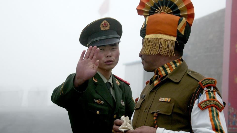 This photo taken on July 10, 2008 shows a Chinese soldier next to an Indian soldier at the Nathu La border crossing between India and China in Sikkim.
