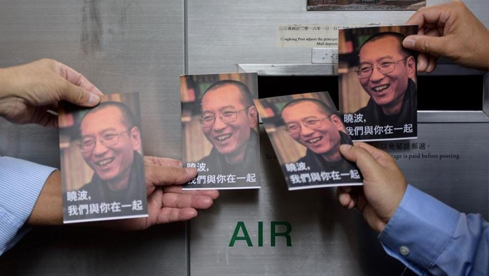 Protestors prepare to post postcards written and addressed to terminally-ill Chinese Nobel laureate Liu Xiaobo (pictured on cards) outside the General Post Office in Hong Kong on July 5, 2017.