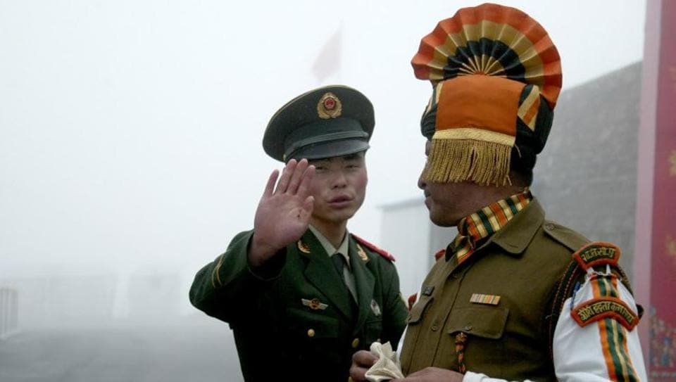 In this photograph taken on July 10, 2008, a Chinese soldier gestures as he stands near an Indian soldier on the Chinese side of the ancient Nathu La border crossing between India and China.