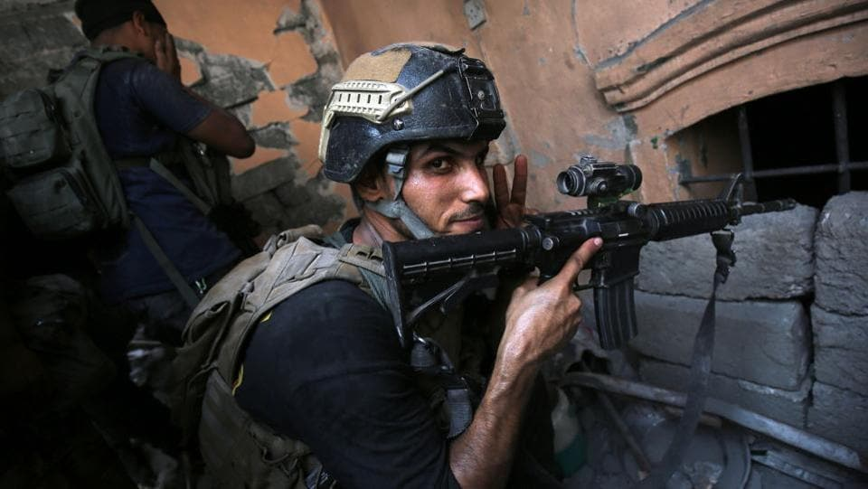 Iraqi Counter-Terrorism Service (CTS) take position inside a house in the Maidan district. Clashes have displaced more than 850,000 people, according to the International Organization for Migration.  (AFP)