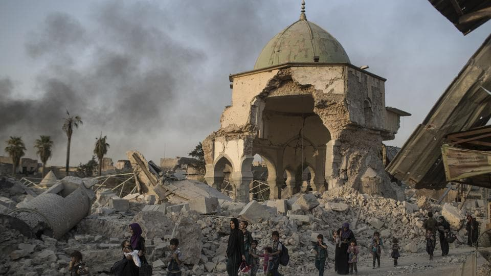 Fleeing Iraqi civilians walk past the heavily damaged al-Nuri mosque as Iraqi forces continue their advance against Islamic State militants in the Old City of Mosul, Iraq. As Iraqi forces continued to advance on the last few hundred square kilometers of Mosul held by the Islamic State group, the country's Prime Minister said Tuesday the gains show Iraqis reject terrorism.  (AP)