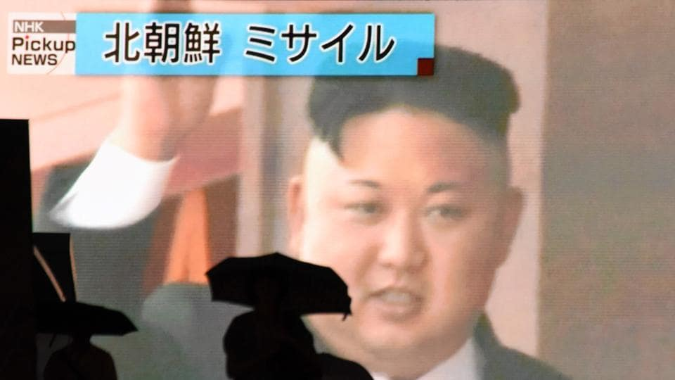 Pedestrians walk past a huge screen in Tokyo broadcasting file news footage of North Korean leader Kim Jong-Un.