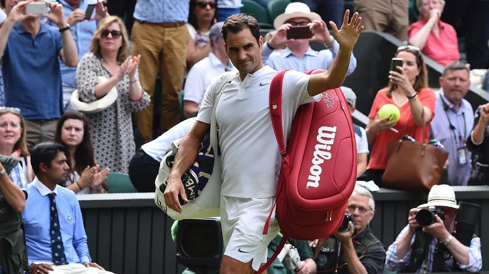 Roger Federer waves as he leaves the court after Ukraine's Alexandr Dolgopolov retired during their men's singles first round match on the second day of the 2017 Wimbledon Championships.