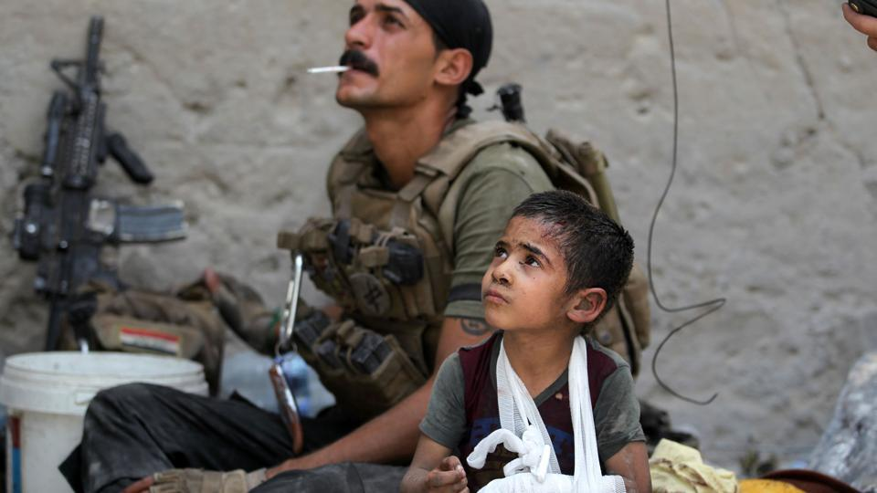 Omar, a young wounded Iraqi boy whose family was killed in the ongoing battles to oust the Islamic State (IS) group from Mosul, sits with members of the Counter Terrorism Services (CTS) as they help him to flee the Old City of Mosul. (AFP)