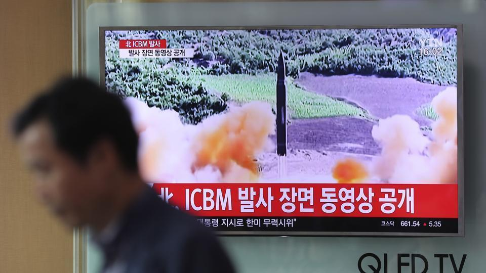 A man walks by a TV screen showing a local news program reporting about North Korea's missile firing on July 5, 2017.