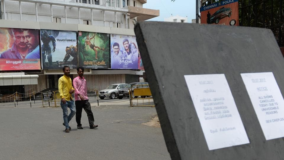 People walk past a closed cinema amid a shutdown called to protest the implementation of GST in Chennai.