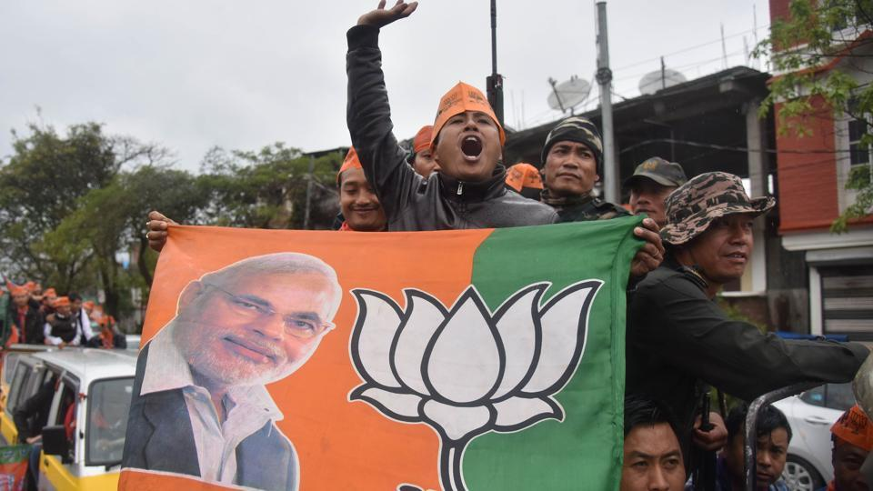 Supporters of the Bharatiya Janata Party (BJP) wave their flags as they celebrate state assembly elections results in Imphal, Assam, on March 11, 2017.
