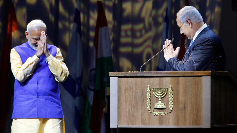 Israeli Prime Minister Benjamin Netanyahu (R) greets his Indian counterpart Narendra Modi during a meeting with Indian community in the Israeli coastal city of Tel Aviv, on July 5, 2017.  Modi addressed a gathering of Jewish people of Indian origin settled in Israel announcing relaxations in the procurement of OCIcards for Indian origin persons who have undergone compulsory military service in Israel. (Gil Cohen-Magen / AFP)