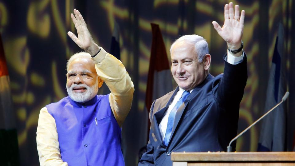 Israeli Prime Minister Benjamin Netanyahu (R) shakes hands with his Indian counterpart Narendra Modi during a meeting with Indian community in the Israeli coastal city of Tel Aviv, on July 5, 2017. Prime Minister Narendra Modi arrived in Israel for what he called a