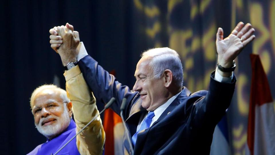 Israeli Prime Minister Benjamin Netanyahu (R) holds hands with his Indian counterpart Narendra Modi during a meeting with Indian community in the Israeli coastal city of Tel Aviv.