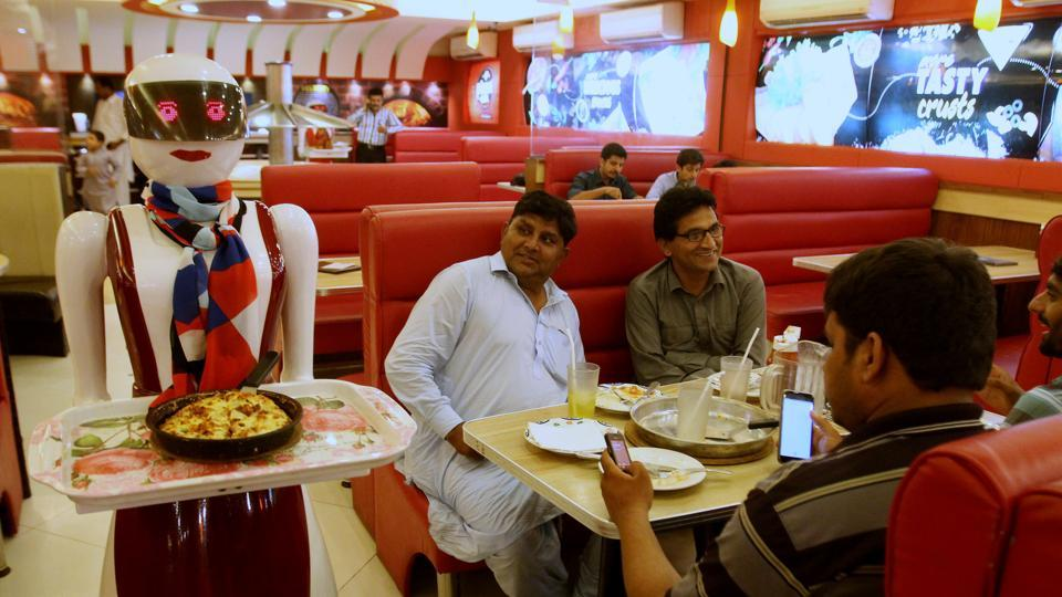 A robot waitress serves food to customers at a pizza restaurant in Multan, Pakistan.