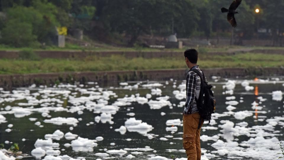 A boy looks at the foam formation on the Mutha river in Pune.