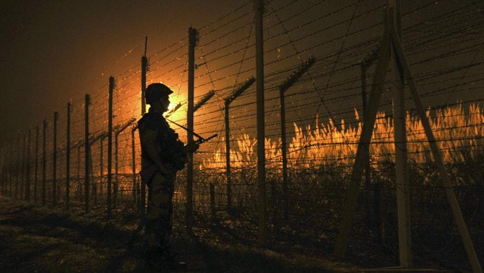 Border Security Force (BSF) soldier standing guard during a night patrol near the fence at the India-Pakistan International Border at the outpost of Akhnoor sector, on October 2, 2016.