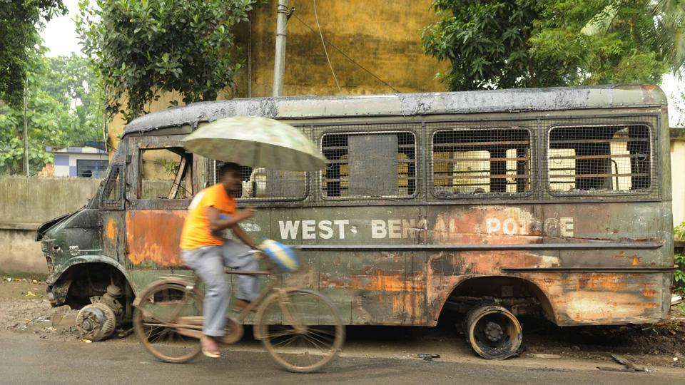 A man cycles past a damaged police van in Basirhat.