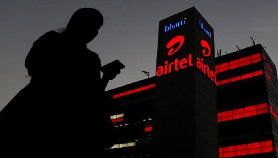 A girl checks her mobile phone as she walks past the Bharti Airtel office building.