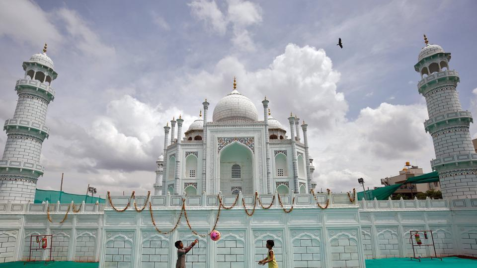In this photo taken on July 06, 2017 children play with a ball in front of a replica of the Taj Mahal built at a fair ground in Bengaluru. (Abhishek Chinappa/REUTERS)