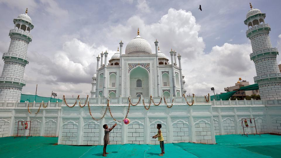 Children play with a ball in front of a replica of the Taj Mahal built at a fair ground in Bengaluru. (REUTERS)