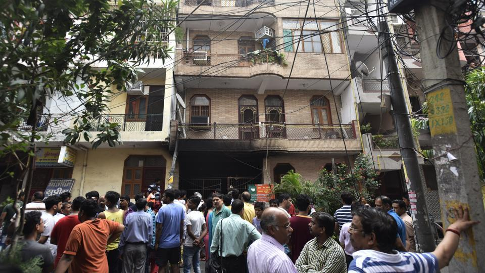 Local residents gather outside the building in Dilshad Colony where the incident took place on Friday.