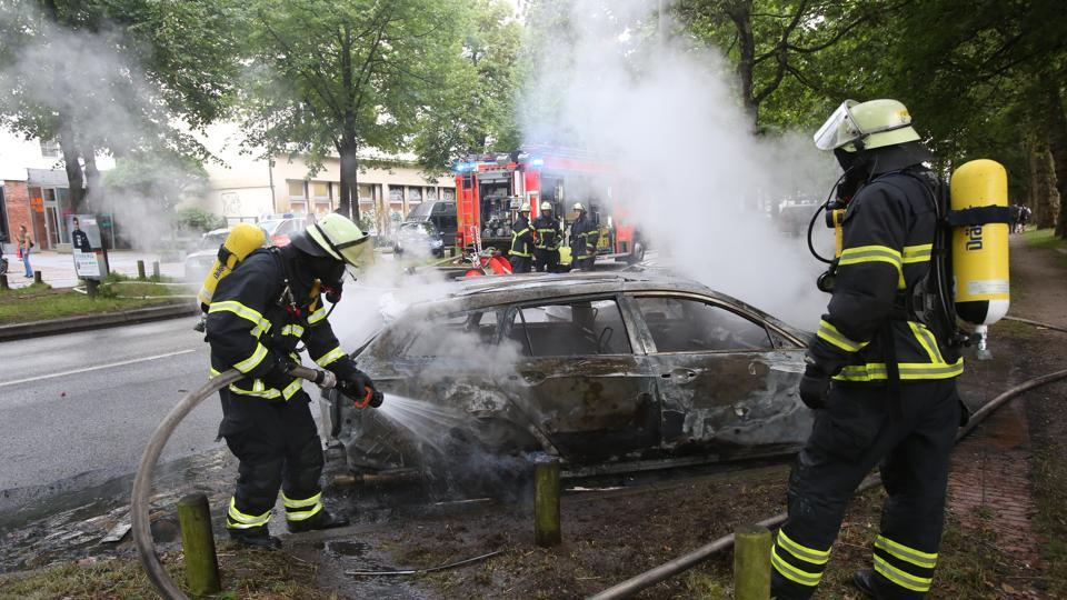 Firefighters put out a fire during a protest against the upcoming G-20 summit in Hamburg, Germany, Friday July 7, 2017. The leaders of the group of 20 meet Friday and Saturday in Hamburg.