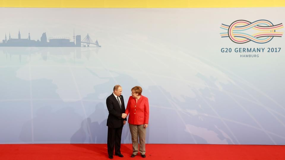 German Chancellor Angela Merkel welcomes Russia's President Vladimir Putin as he arrives for the summit in Germany.  (AFP)
