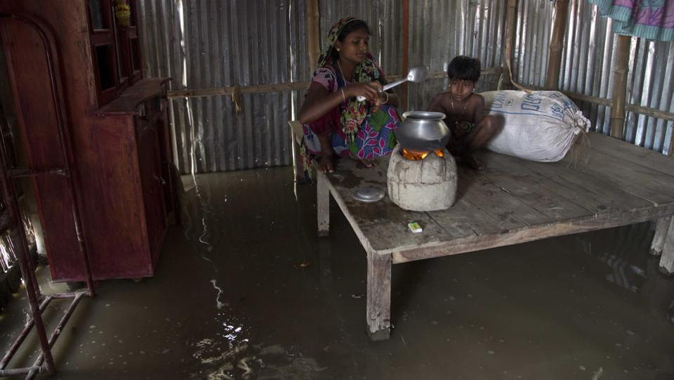 A  woman prepares food in her flooded house in Burgaon, 80 kilometers (50 miles) east of Gauhati. The water levels of Brahmaputra river and its tributaries crossed danger level mark at several areas in the state caused by incessant rains in past couple of days. (Anupam Nath / AP)