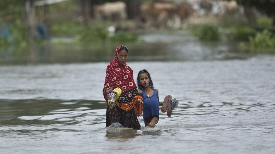 A woman and a child cross a waterlogged street at Burgaon, 80 kilometers (50 miles) east of Gauhati. Northeast's biggest city, Guwahati, also came under threat as the water level of the swelling Brahmaputra river crossed the danger level mark on Wednesday afternoo (Anupam Nath / AP)