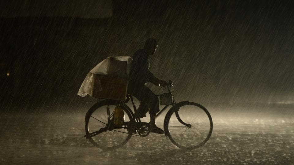 A man rides on a bike as heavy rain falls in Jalandhar. (AFP)
