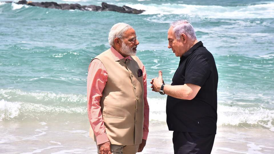 Modi and Netanyahu seen standing ankle deep in the waters with waves lapping at their feet, engaged in what seemed like an intense discussion.  (AFP)