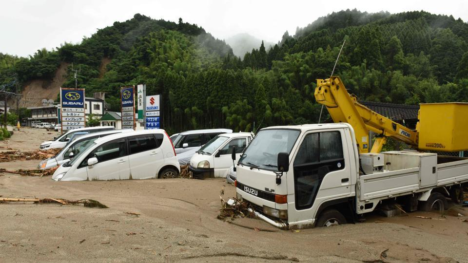 Vehicles are buried in the mud following heavy flooding in Asakura, Fukuoka prefecture.