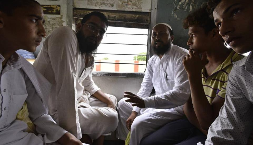 Junaid's  two brothers (first and second from right) travel on an EMU train at Ballabhgarh railway station in Haryana's Faridabad district .
