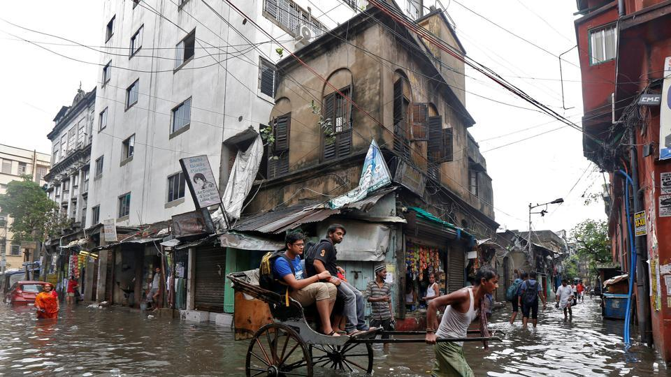 A rickshaw puller transports passengers through a waterlogged street after heavy rain in Kolkata, India on July 7, 2017. (Rupak De Chowdhuri/REUTERS)