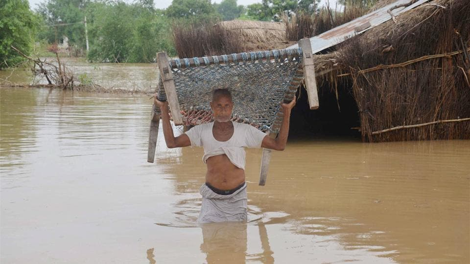 A man lifts a cot as he wades through flood waters to shift to a safer place after his house got partially submerged following heavy rains at a village in Vindhyachal in Mirzapur. (PTI)
