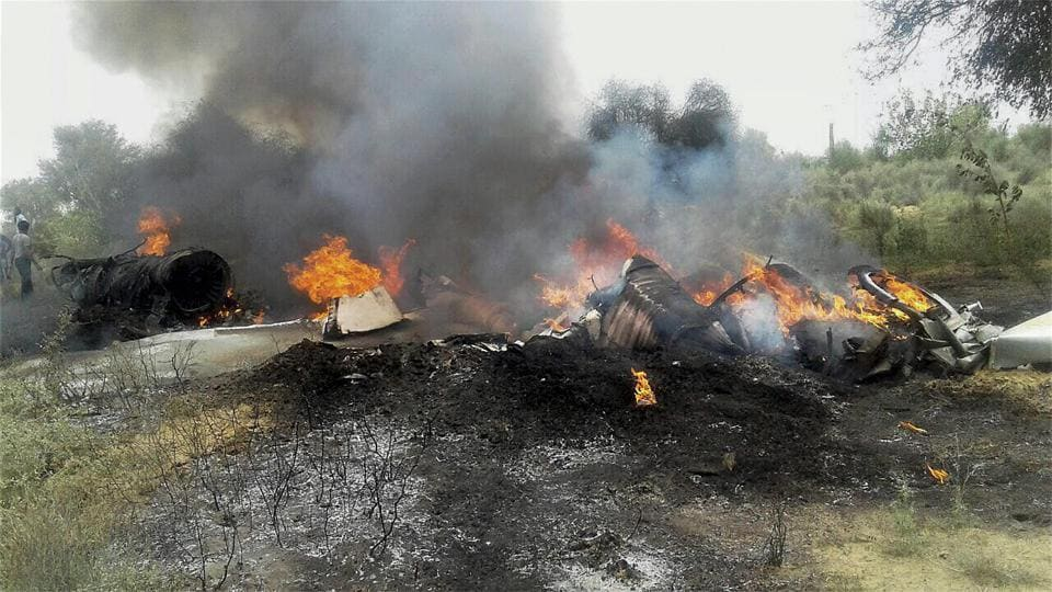 People watch the burning wreckage of MiG-23 trainer aircraft of the Indian Air Force after it crashed in the Balesar near Jodhpur. Both pilots of the aircraft ejected safely. (PTI)