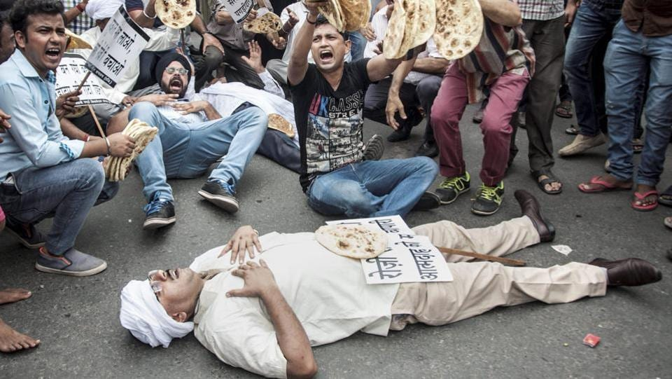 Hundreds of traders (Pagdi tenants), holding placards and chapati (bread), shout slogans during a protest against the Delhi Rent Control Act at Town Hall, Chandni Chowk in New Delhi. (PTI)