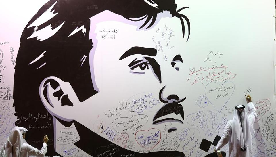 Qataris write comments on a wall bearing a portrait of Qatar's emir, Sheikh Tamim bin Hamad Al Thani, which has become the symbol of Qatari resistance during the month-long row between Doha and neighbouring countries, on July 6, 2017.