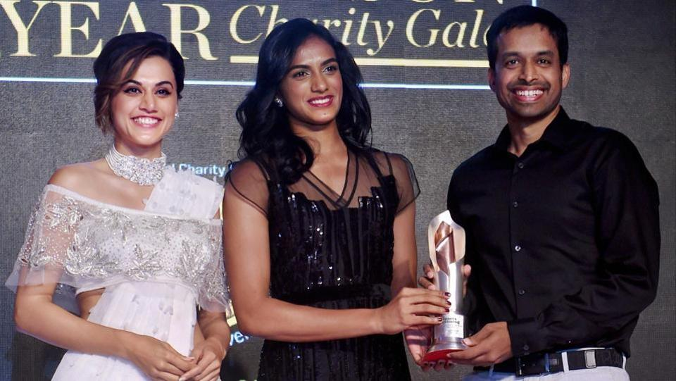 Badminton coach Pullela Gopichand being felicitated by badminton player P.V.Sindhu and actress Tapsee Pannu during the 'Sportsperson of the Year' charity gala awards in Mumbai. (PTI)